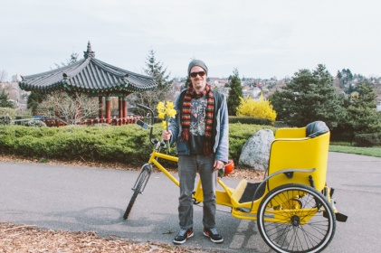 """I was out on the farm but right now I'm drawn to the city right so I'm doing this."" Sam runs a fleet of pedicabs in Seattle. I saw him picking flowers and he was kind enough to let me take his photo."
